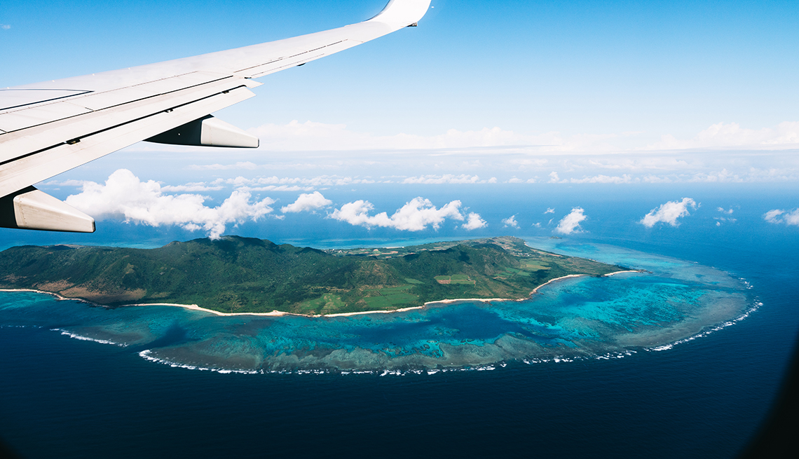 Flying over a tropical island with coral reefs