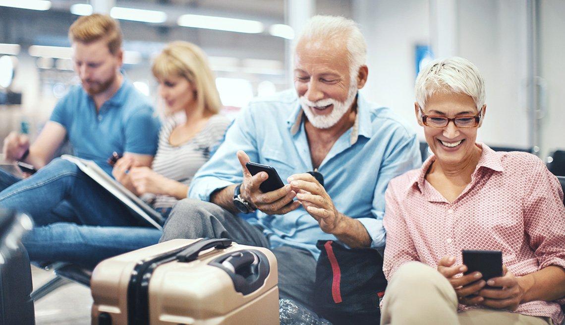 Grupo de personas usan sus aparatos electrónicos mientras esperan por un tren