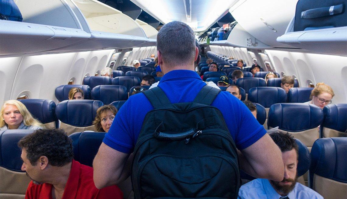 Hombre abordando un avión lleno de gente