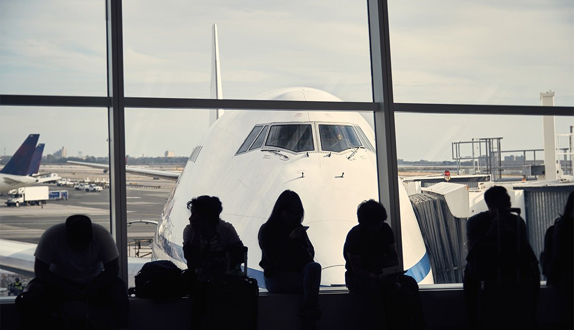 Passengers are waiting in an airport terminal to board their outgoing commercial airplane flight