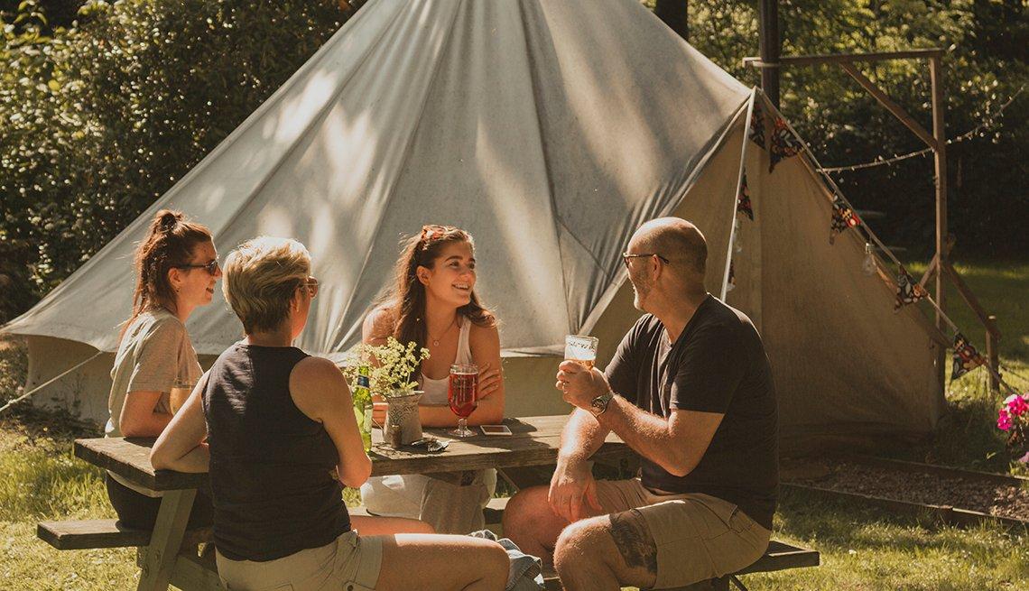 4 integrantes de una familia están sentados en un banco de picnic mientras acampan en su patio trasero