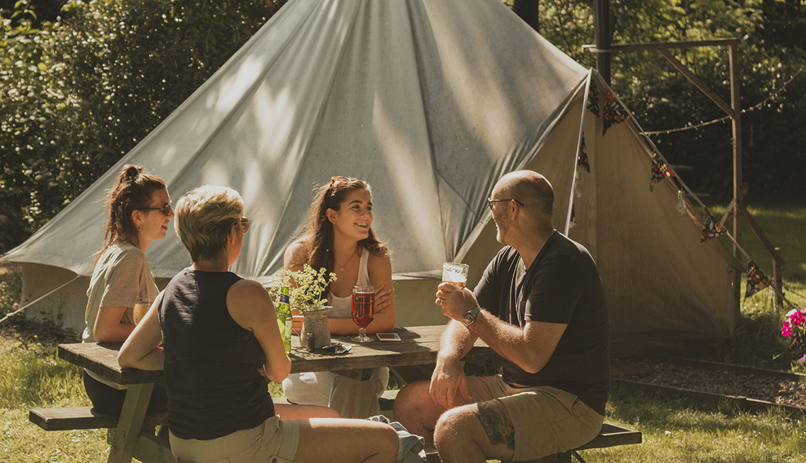 Family of four are sitting at a picnic bench while camping in their backyard