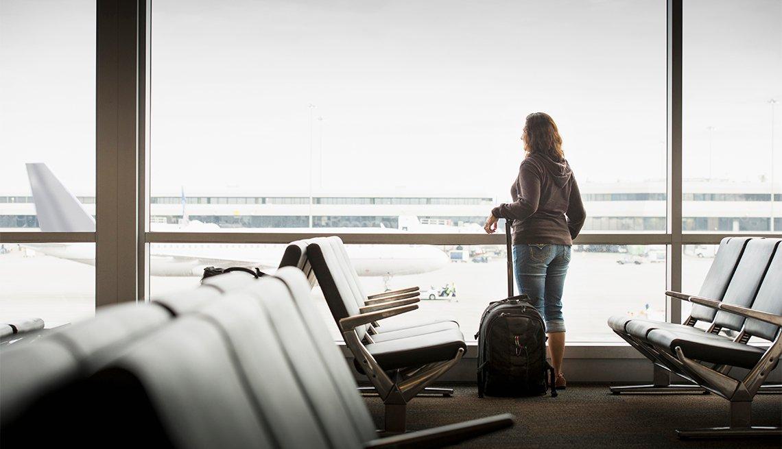 Mujer ve por la ventana de un aeropuerto