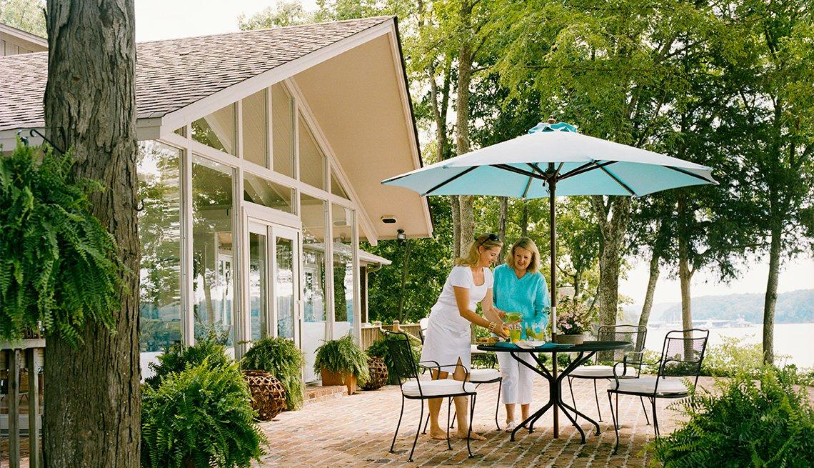 Dos mujeres vierten bebidas mientras están en el comedor de un patio exterior