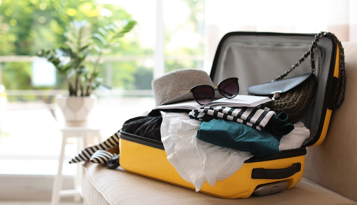 Open yellow suitcase with different clothes packed for a trip