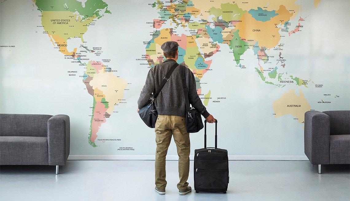 Hombre que viaja mira un mapa del mundo en una pared