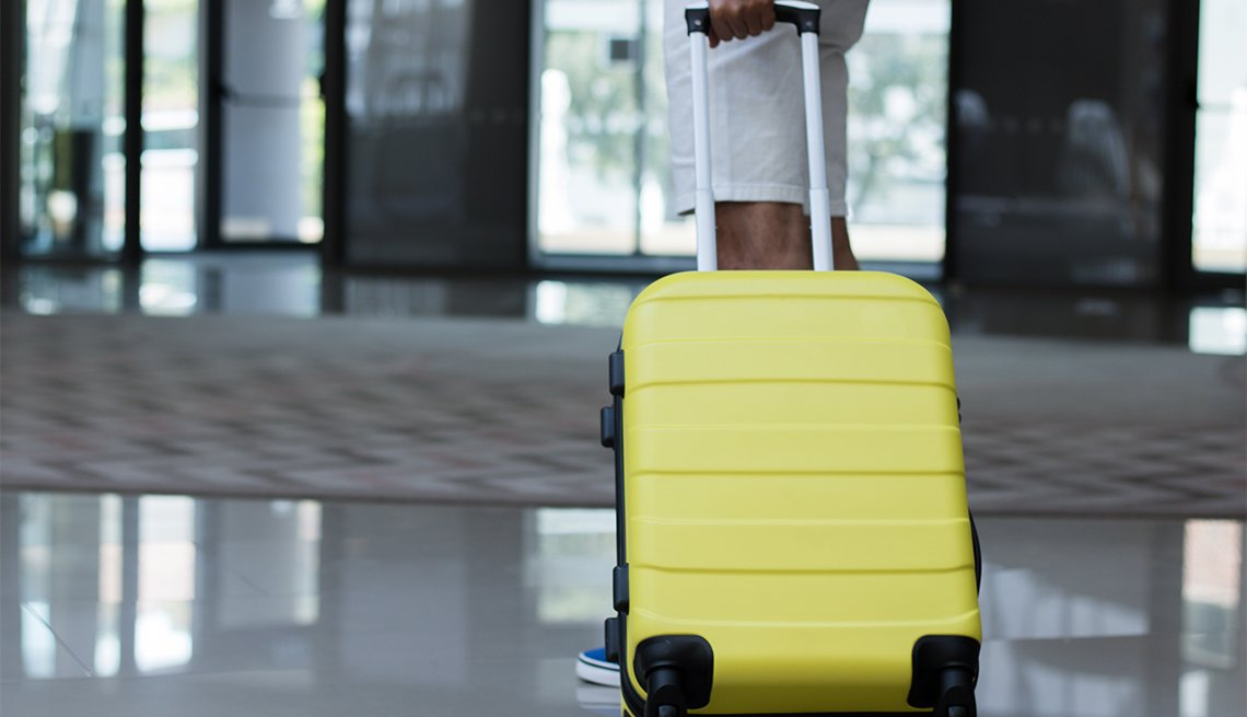 Man with yellow suitcase waiting in a hotel hallway