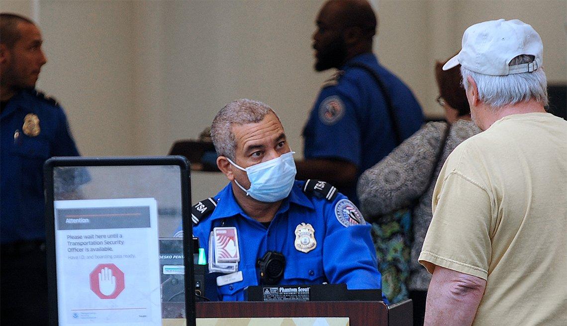 Agente de la TSA observa a un pasajero desde el puesto de control de un aeropuerto