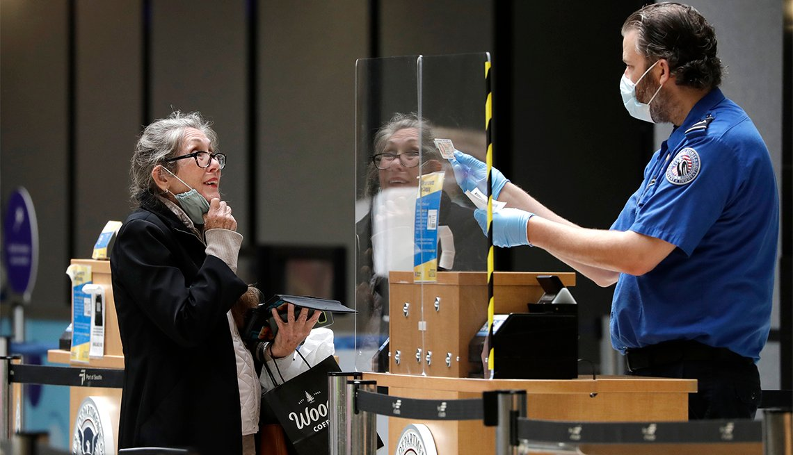A traveler pulls down her protective mask as a TSA agent compares her face to her identification at a security entrance at Seattle-Tacoma International Airport Monday, May 18, 2020