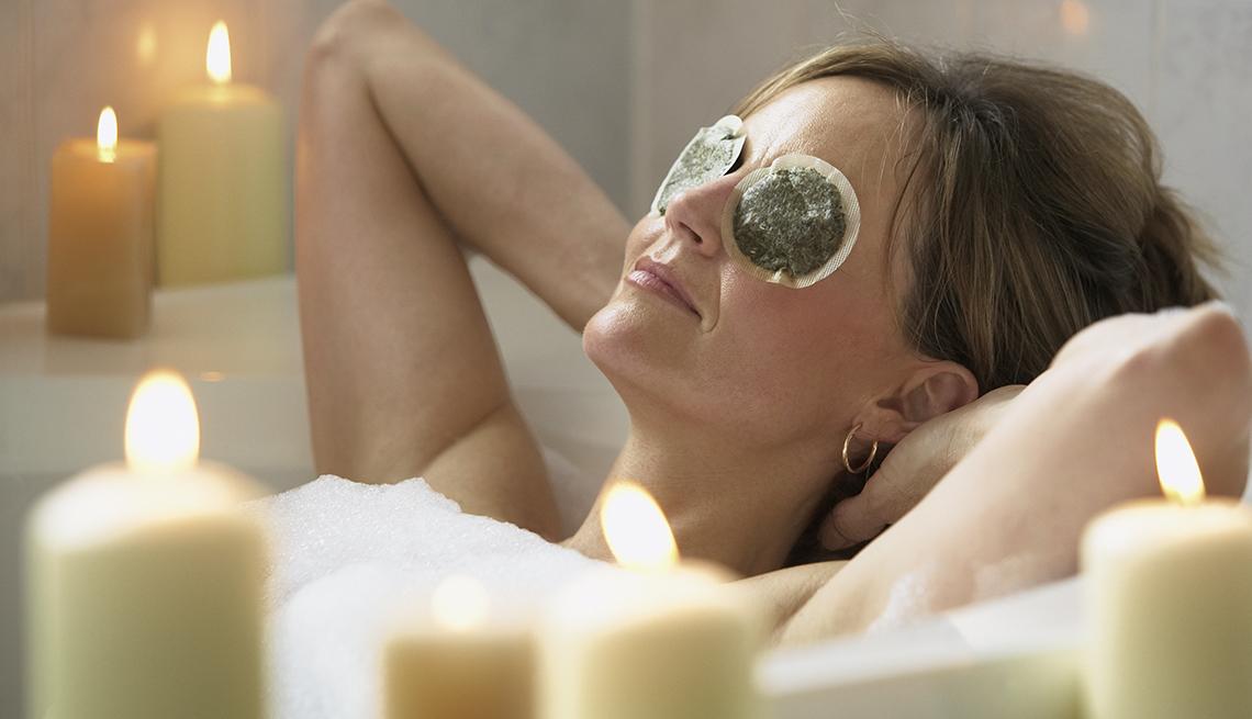Mujer relajada en la bañera con bolsitas de té sobre los ojos