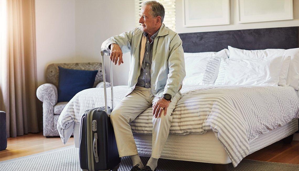 Foto de un hombre sentado en la cama en su habitación de hotel