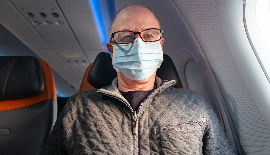 man sitting on a commercial jetliner, wearing protective mask