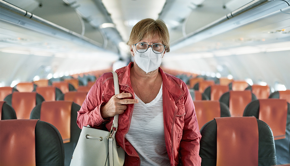 woman in eyeglasses, protective mask, and casual clothing exiting empty airplane