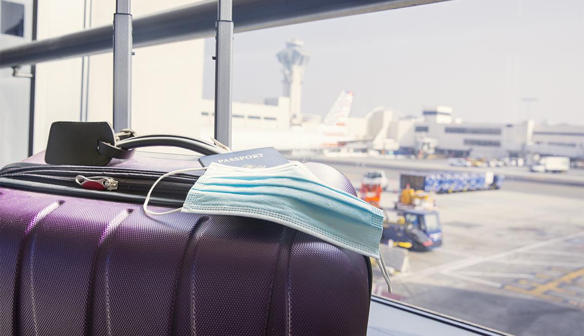 Pasaporte y mascarilla quirúrgica sobre una maleta