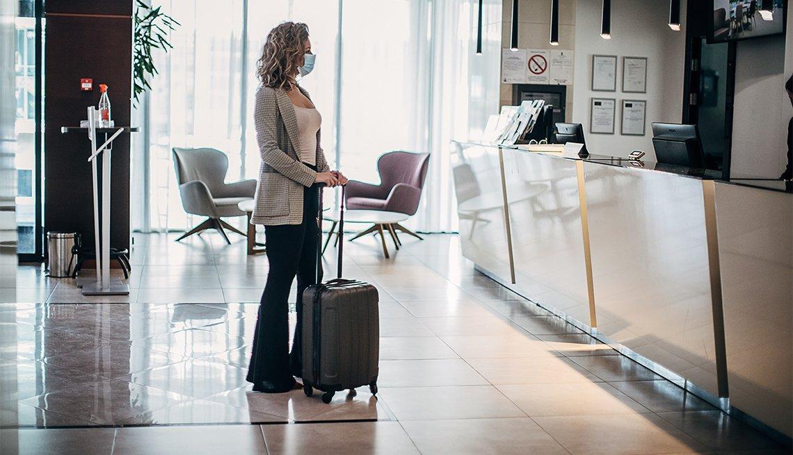 Mujer espera para registrarse en la recepción de un hotel