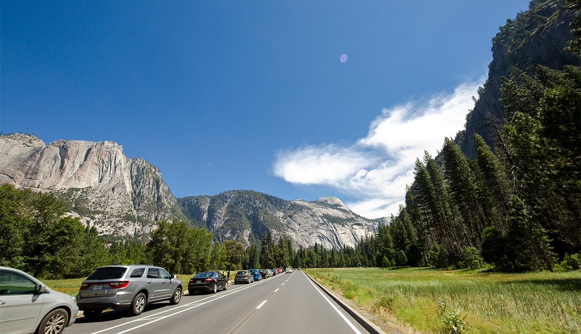 a line of cars drive toward Yosemite National Park entrance