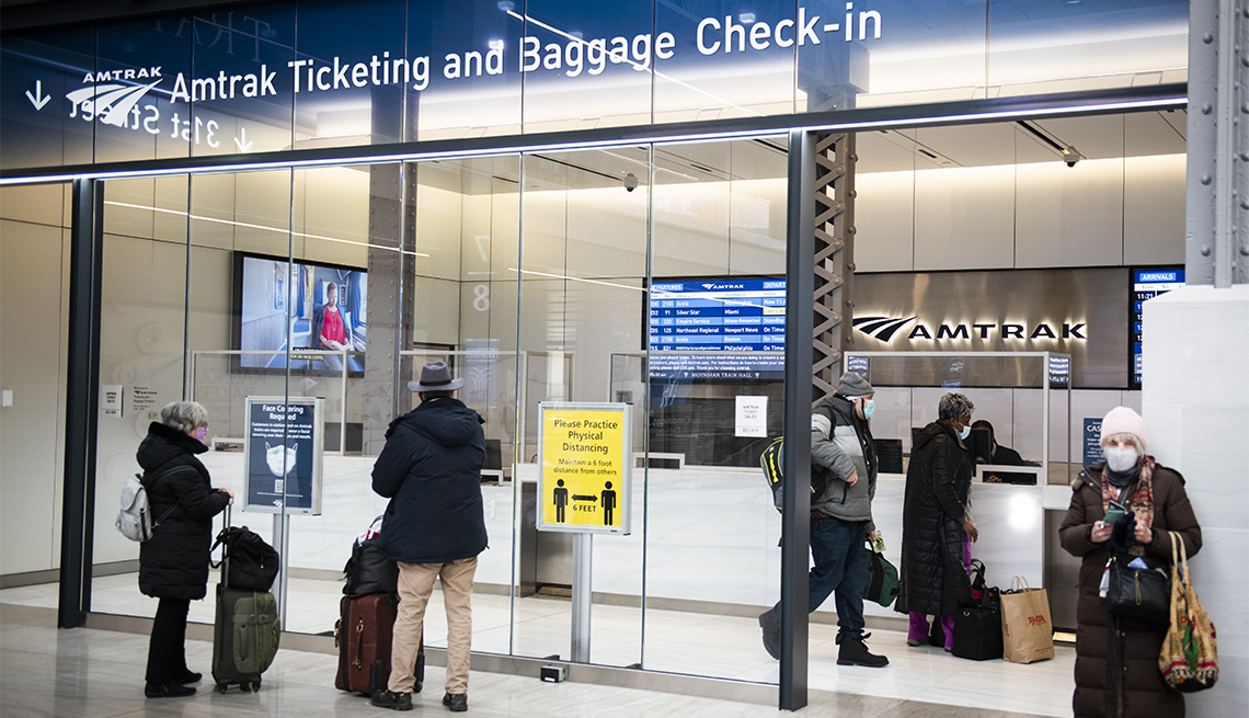 Passengers wearing protective masks wait outside an Amtrak ticketing area at Moynihan Train Hall at Pennsylvania Station in New York, U.S., on Friday, Jan. 8, 2020