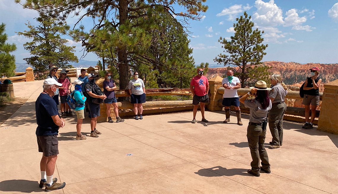 Tourists, wearing masks and keeping social distance, listen to instructions given by the Bryce Canyon park rangers before starting the 1.3 miles Najavo trail hike inside Bryce Canyon National Park, Utah on August 26, 2020