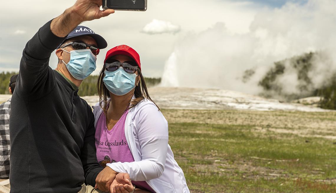a couple takes a selfie as Old Faithful