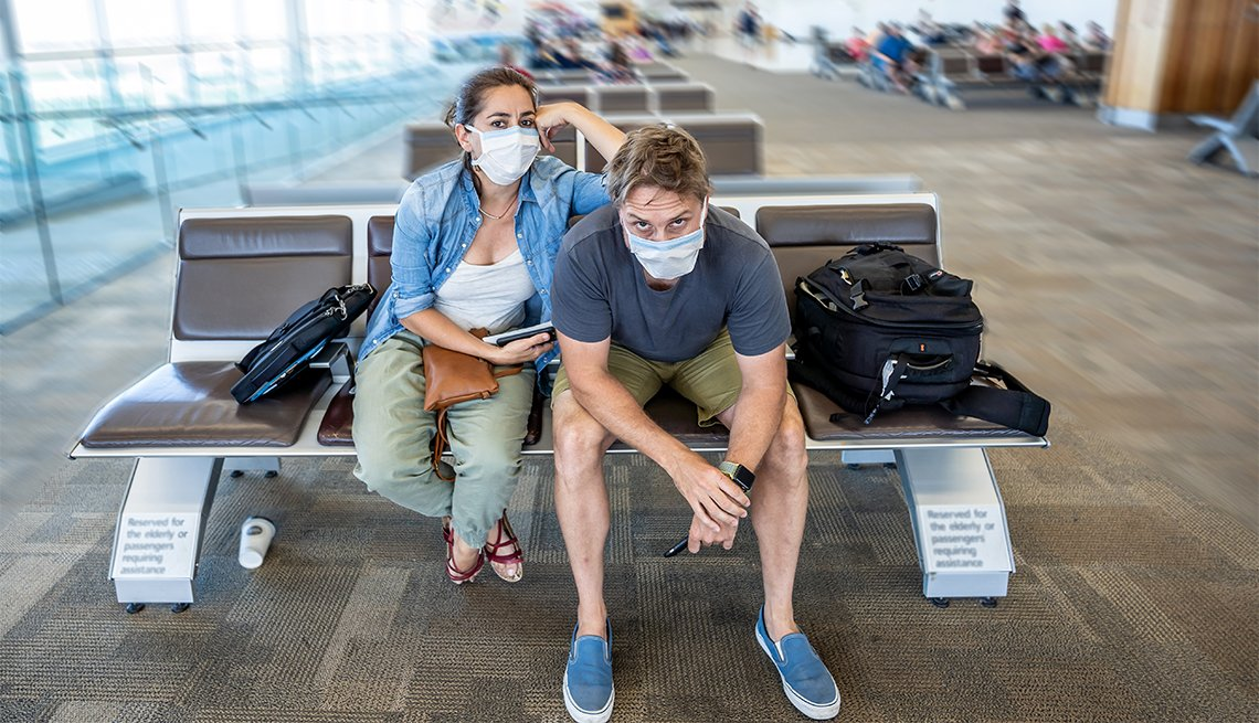 travelers wearing masks at airport terminal