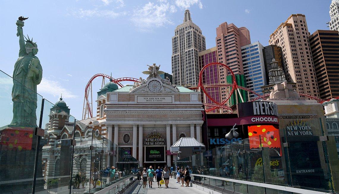 Visitors walk on a pedestrian bridge between MGM Resorts International properties New York-New York Hotel & Casino and MGM Grand Hotel & Casino on the Las Vegas Strip