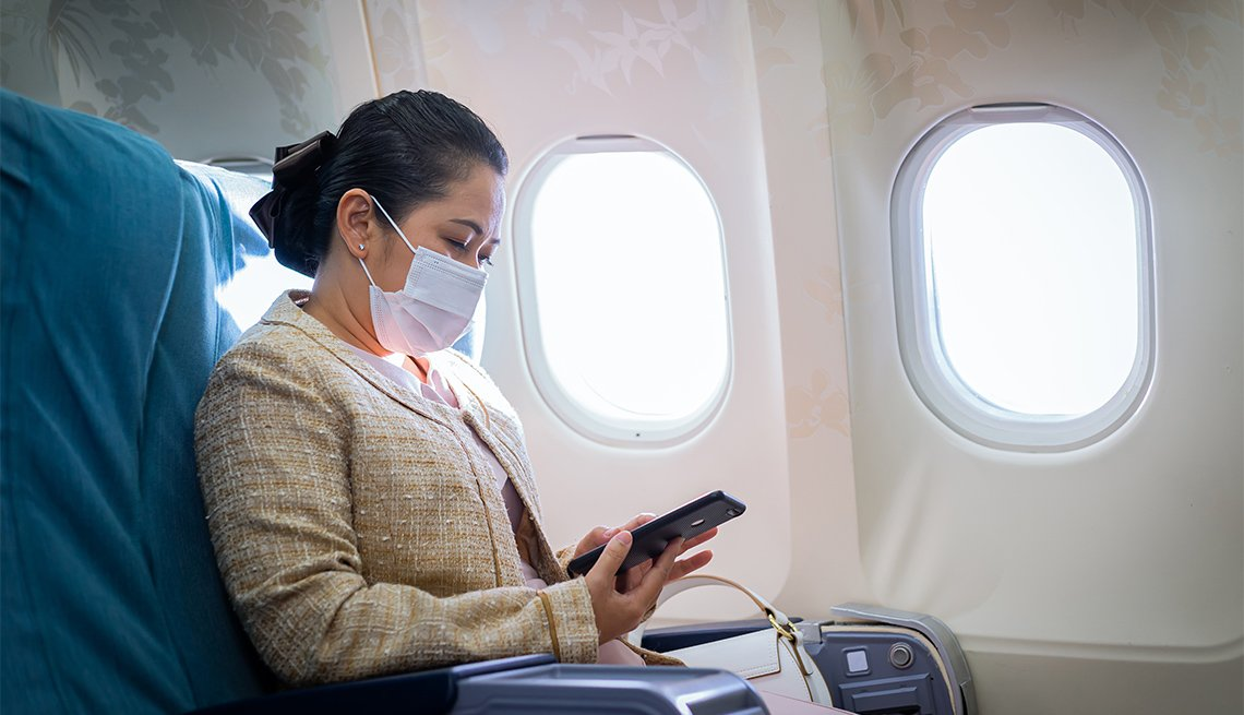 Business woman using a smartphone in an airplane
