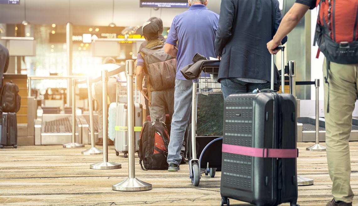Pasajeros alineados en el aeropuerto para chequear su equipaje