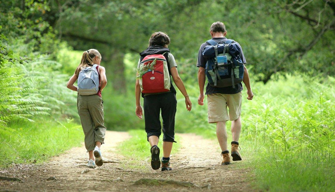 Familia camina por un sendero entre los árboles