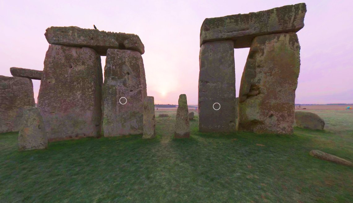 screenshot of stonehenge virtual tour showing the sunrise in the distance and several of the standing stones