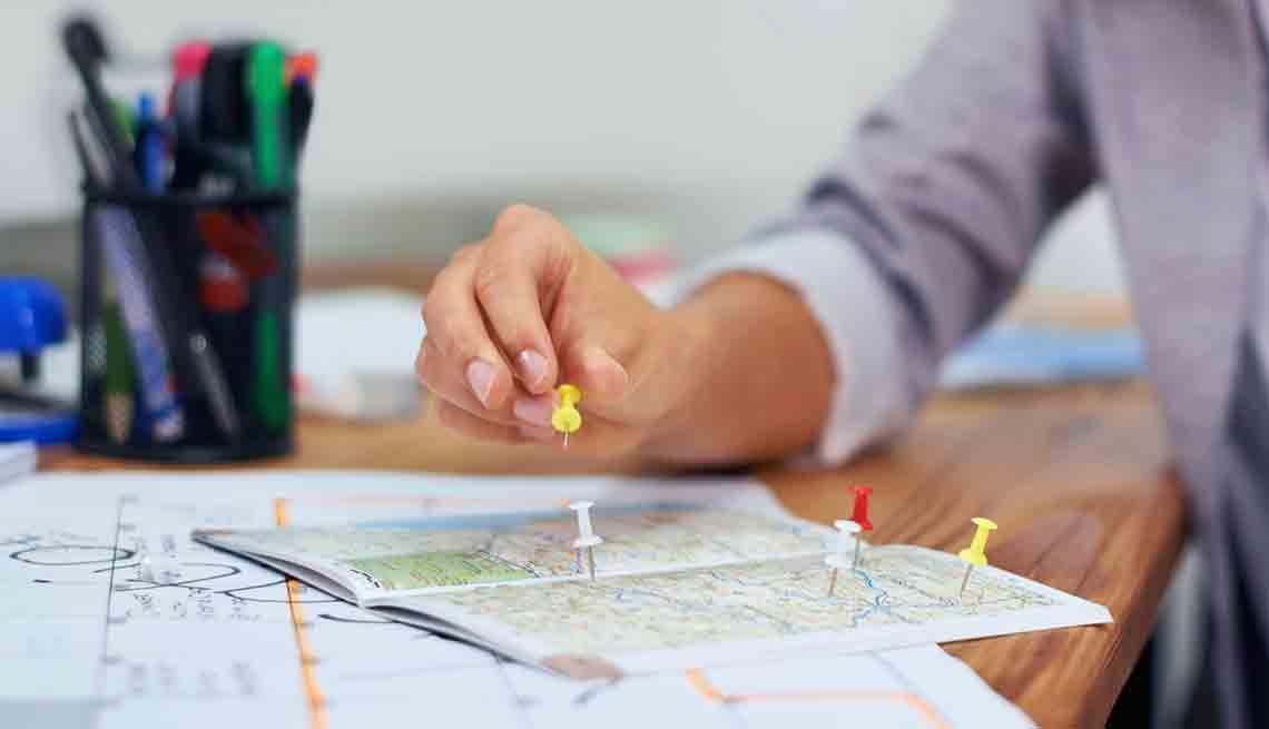 Mujer selecciona destinos en un mapa - 4 razones para acudir a un agente de viaje