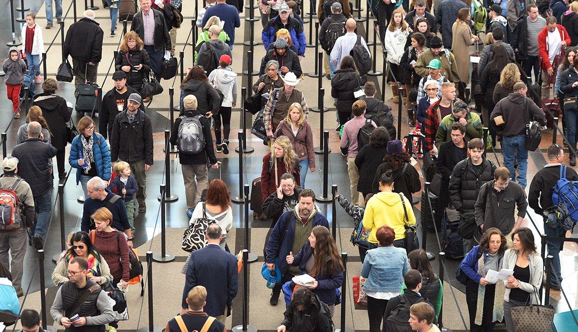 Qué es el PreCheck de la TSA en los aeropuertos - Personas caminando en un aeropuerto