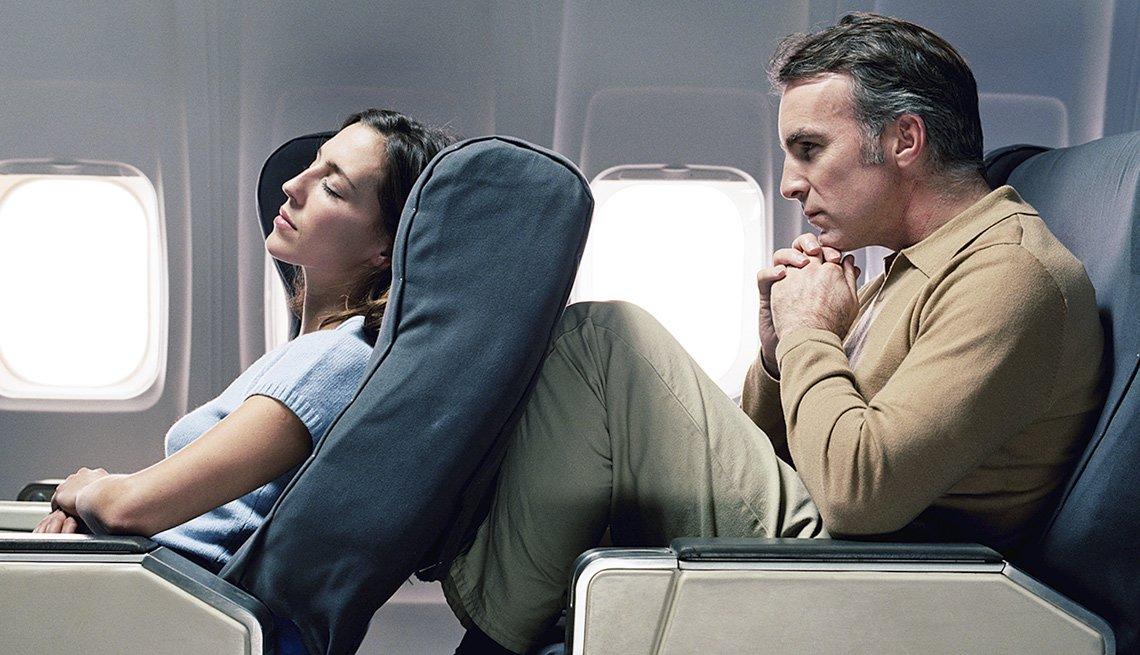 Asiento de avión reclinado de la mujer en las piernas de un hombre