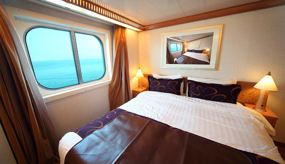 Cabina de un crucero con ventana y cama doble.