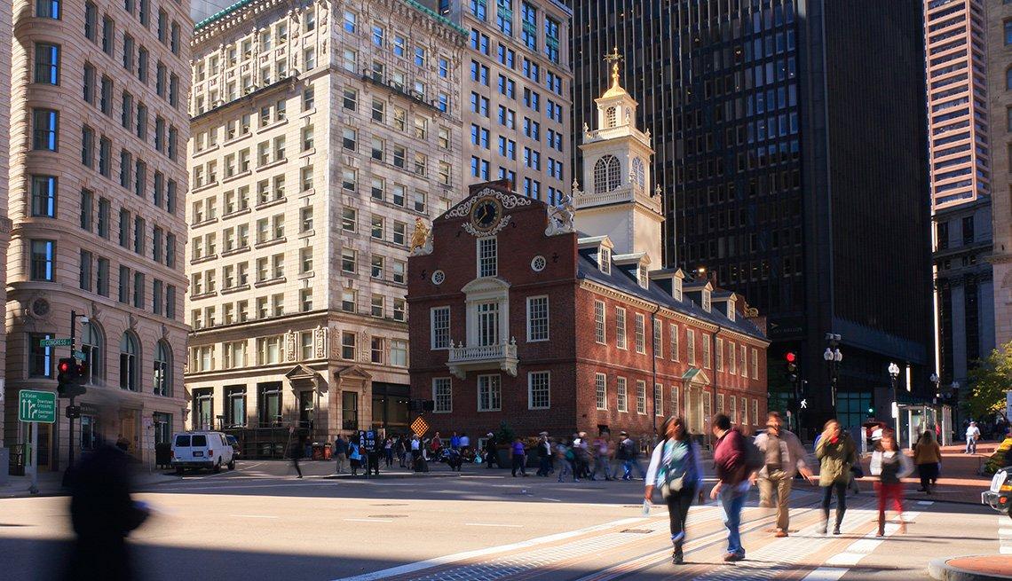 La imagen muestra al Old State House, una edificación antigua, ahora museo de historia, ya personas que cruzan en la concurrida intersección en el centro de Boston, Massachusetts.