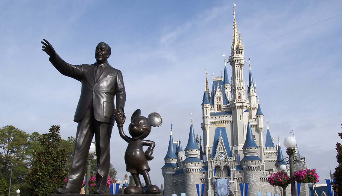 A statue of Walt Disney and Mickey Mouse stands in front of the Cinderella's castle in Disney World