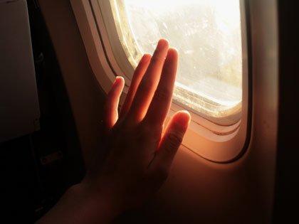 una mano en la ventana de un avión - 6 Lugares donde los gérmenes crecen en un avión
