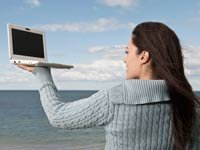 Mujer sostiene una computadora portátil — Dónde encontrar las mejores ofertas para viajar.