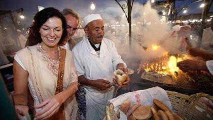 Pareja comiendo en un mercado en Marrakesh, Marruecos - La comida local es clave para entender la cultura de un lugar y de sus tradiciones.