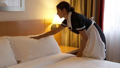 Camarera de un hotel haciendo la cama de una habitación - Confesiones del personal de limpieza de un hotel