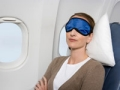 Woman wearing sleep mask on airplane (Alamy)