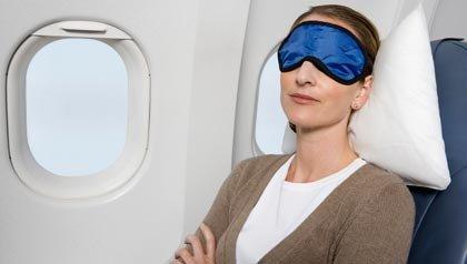Mujer con máscara de sueño en el avión