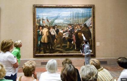 El guía turístico y los turistas que buscan en La rendición de Breda de Velázquez en el Museo del Prado, Madrid, España