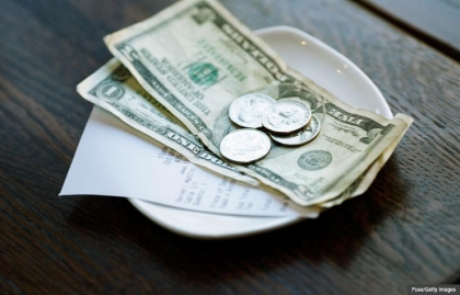 Money and bill in dish on table, Tipping the right amount (Fuse/Getty Images)