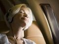 Primer plano de mujer mayor con audífonos y durmiendo en un avión