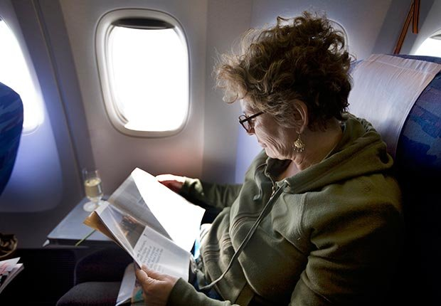 Una mujer leyendo en un vuelo - 6 elementos que usted debe tener en su equipaje de mano.
