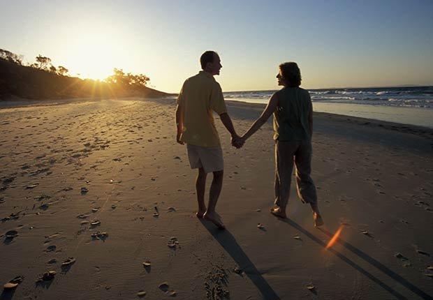 Pareja caminando en la playa - Destinos de vacaciones