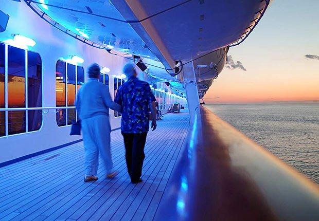 Dos personas caminando en el pasillo exterior de un barco - Guía para planificar un viaje en crucero