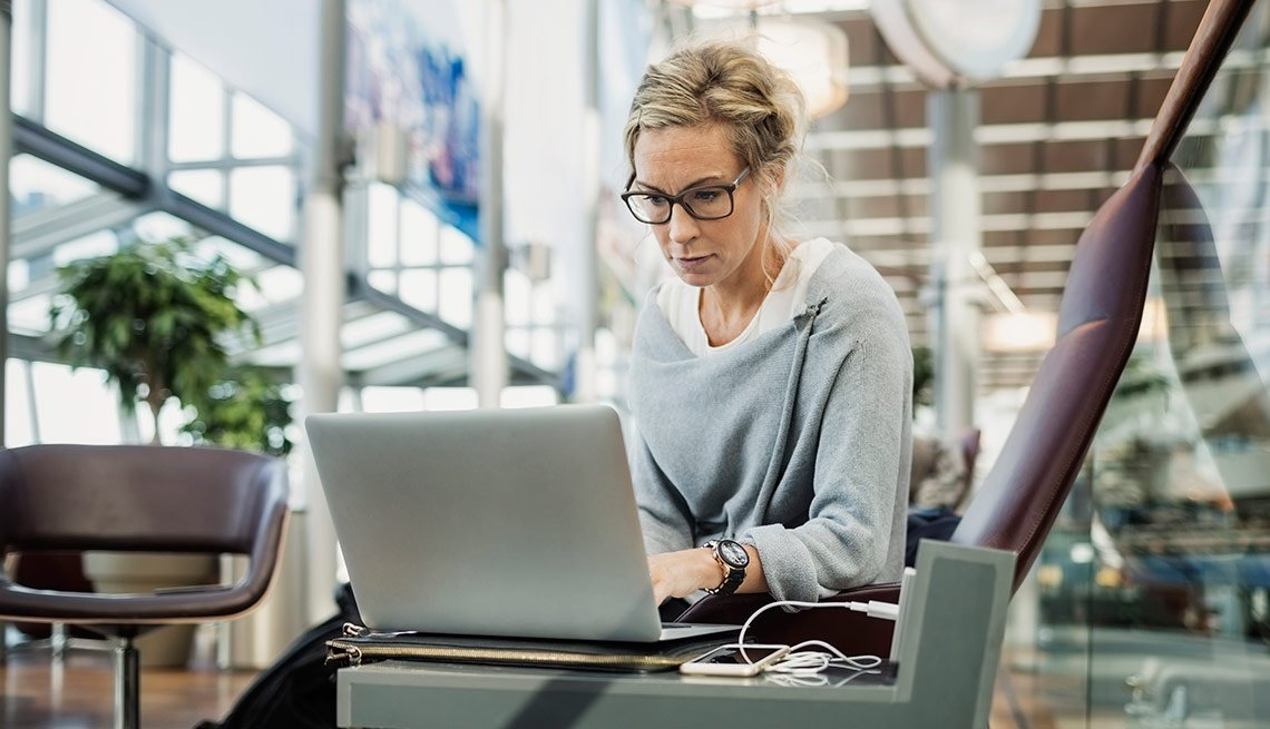 Business woman using laptop at airport lobby