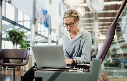 Mujer viendo pantalla de computadora - Maneras de conseguir pasajes aéreos baratos