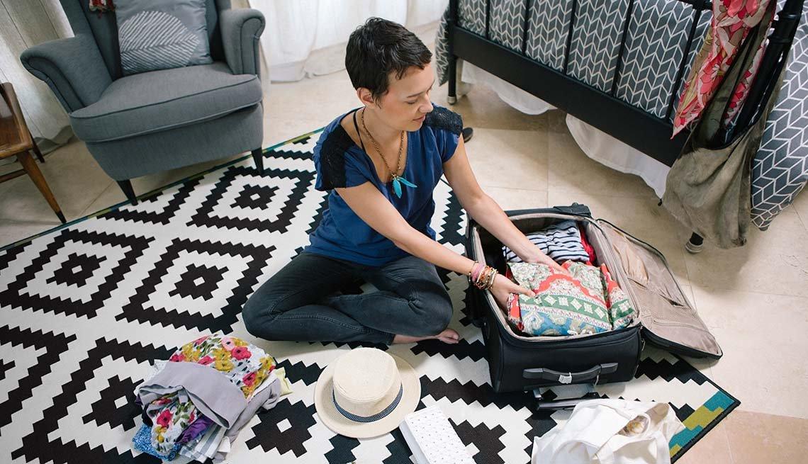 Mujer empacando una maleta de viaje